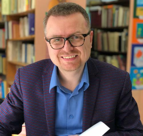 Mężczyzna w okularach podpisujący książkę na tle regałów bibliotecznych.