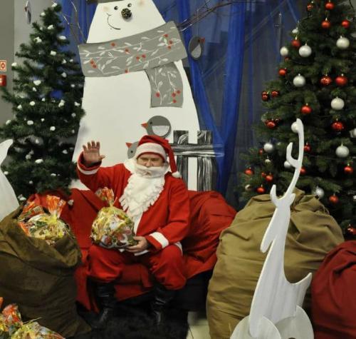 Mikołaj z podniesioną ręką na tle bałwana i choinek. Przed mikołajem prezenty i biały renifer.