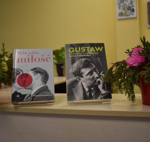 Dwie książki na ustawione na stoliki. Obok książek kwiaty.