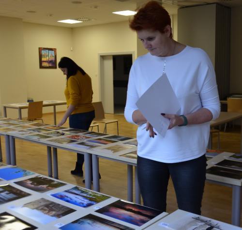 Jury oglądające konkursowe zdjęcia. Na stołach poukładana fotografie.
