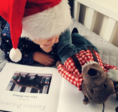 Plakat przedstawia chłopca, ubranego w czapkę Św. Mikołaja, czytającego książkę. Obok chłopca leży maskotka- renifer, w czerwono-białej koszuli w kratkę i granatowe spodnie na szelki.
